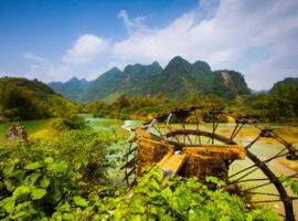 Blick auf die Berge mit Wasserrad im Vordergrund